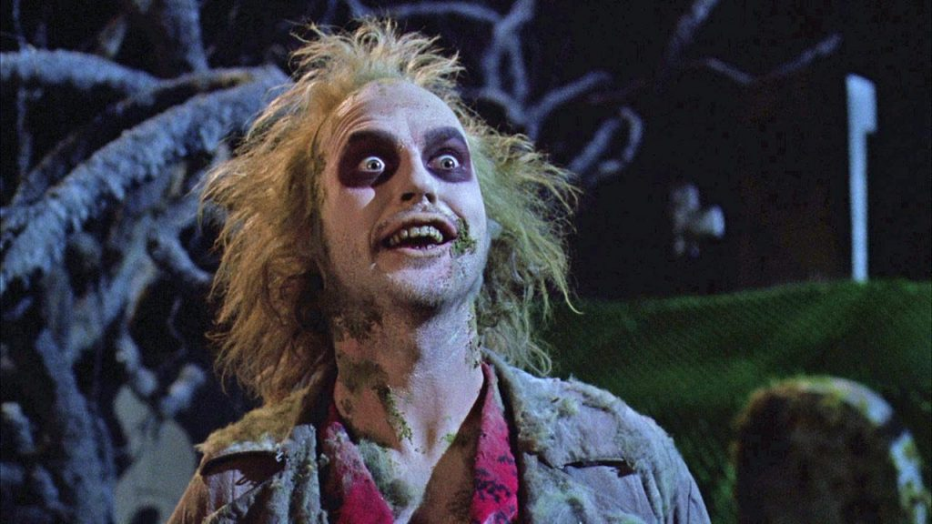 Michael Keaton as Beetlejuice, smiling maniacally and tilting his head up