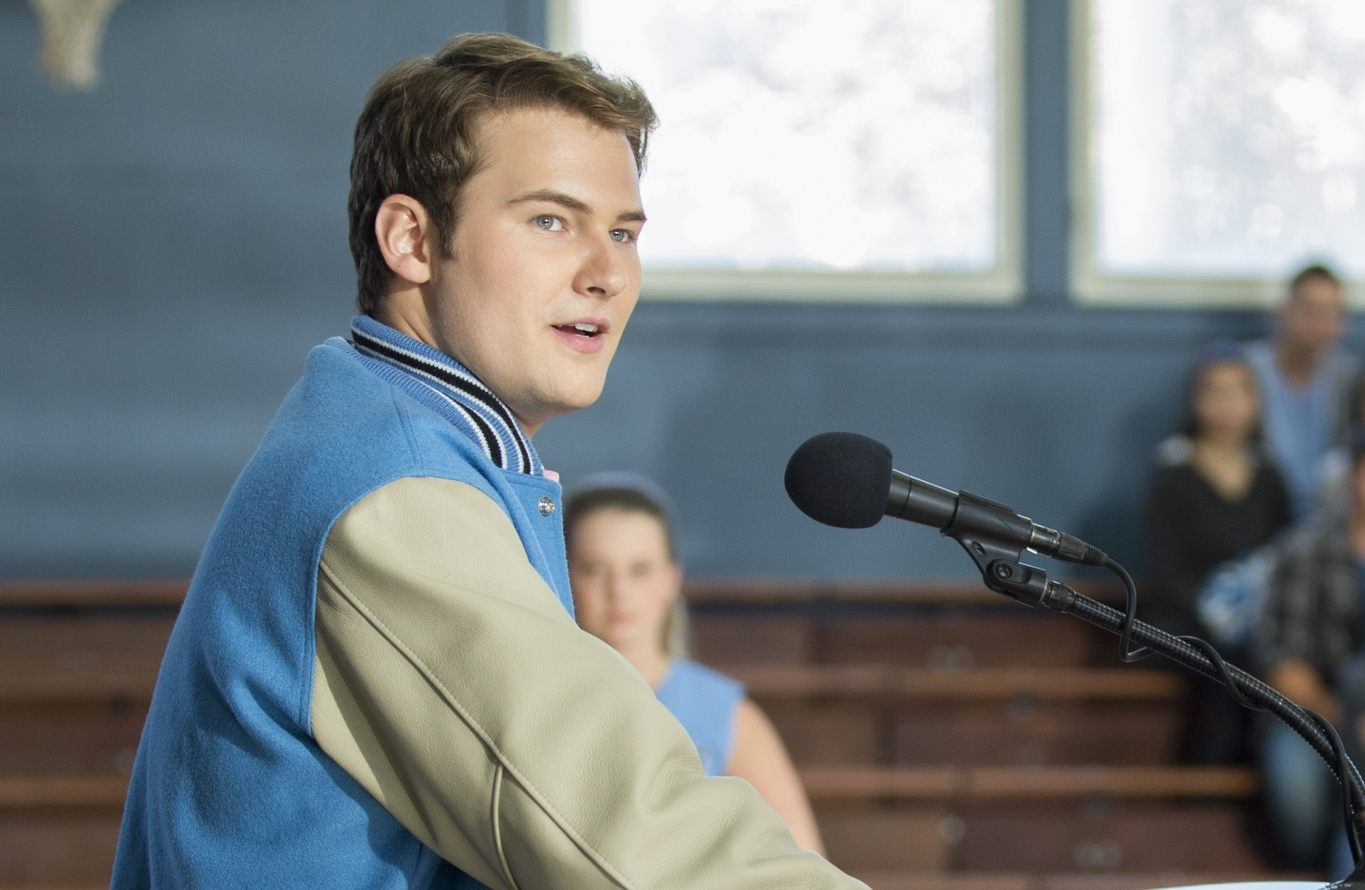 Bryce stands at a microphone in a scene from 13 Reasons Why