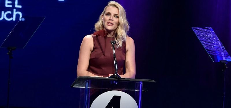 Busy Philipps is on stage standing at a podium.