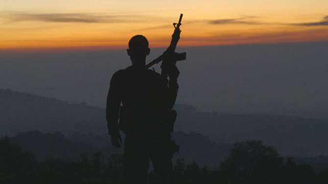 The silhouette of a man holding up a rifle while looking at a sunset
