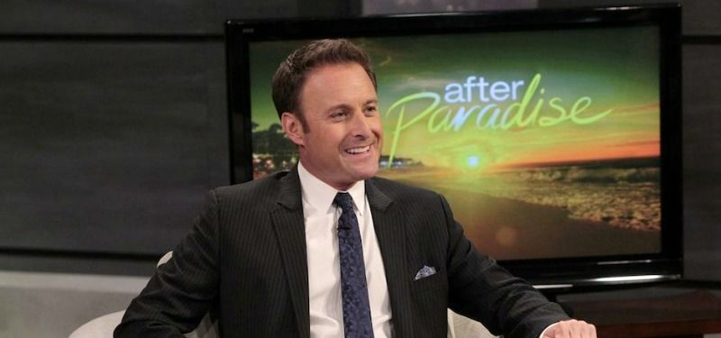 """Chris Harrison is in a suit and smiling in front of a tv that says """"After Paradise."""""""