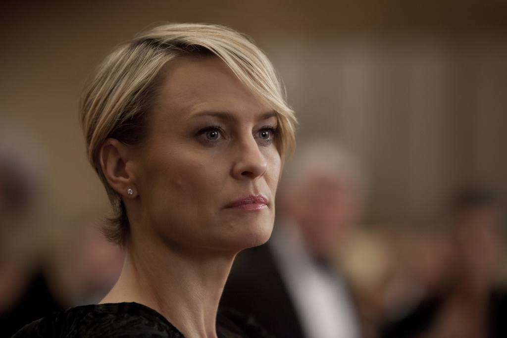 Claire Underwood in a black top, looking off to the right of the frame
