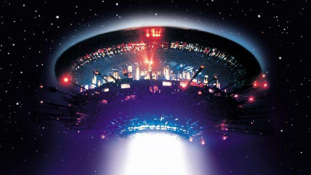 A spaceship, shaped like a tall circular stack, with lights surrounding it on all sides