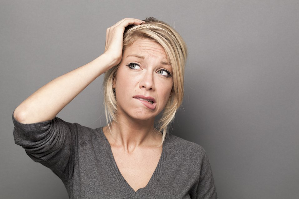 Woman who is holding her head and looking worried
