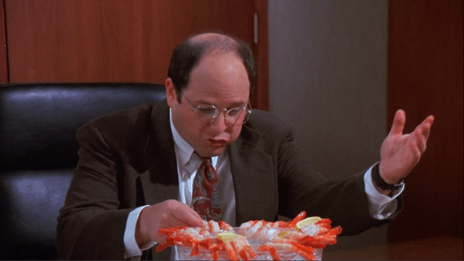 George Costanza disregards office etiquette and dives into a bowl of shrimp