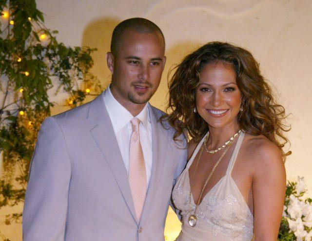 Jennifer Lopez poses and smiles with then-husband Cris Judd at a restaurant opening in 2002.