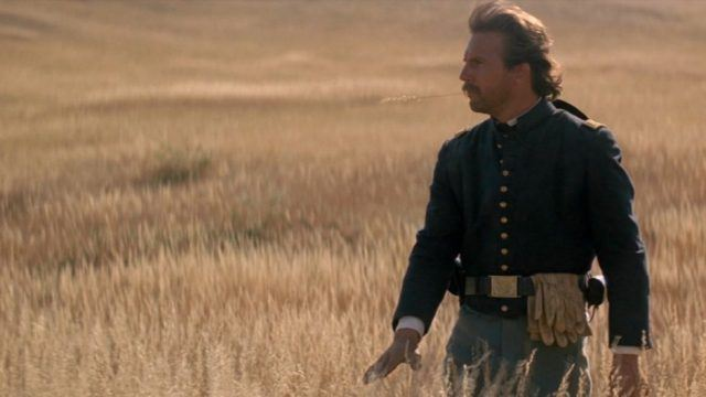 Kevin Costner dressed in a military uniform, walking through a grassy meadow