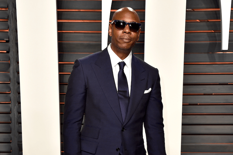 Dave Chappelle poses on the Vanity Fair red carpet in sunglasses