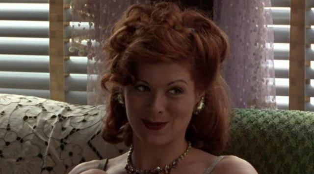 Debra Messing is smiling while sitting on a couch.