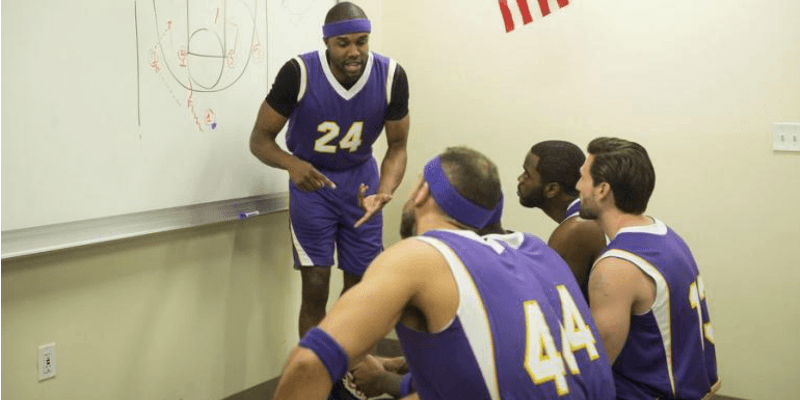 DeMario Jackson is with his basketball team mates and talking to them in front of a board.