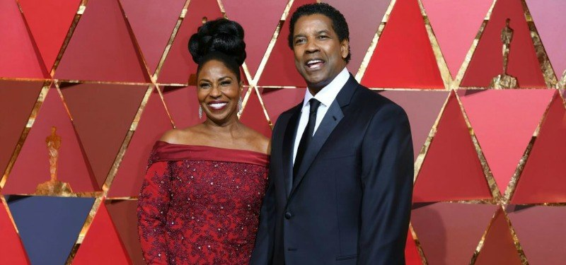 Denzel Washington is in a black suit with Pauletta who is in a red dress.