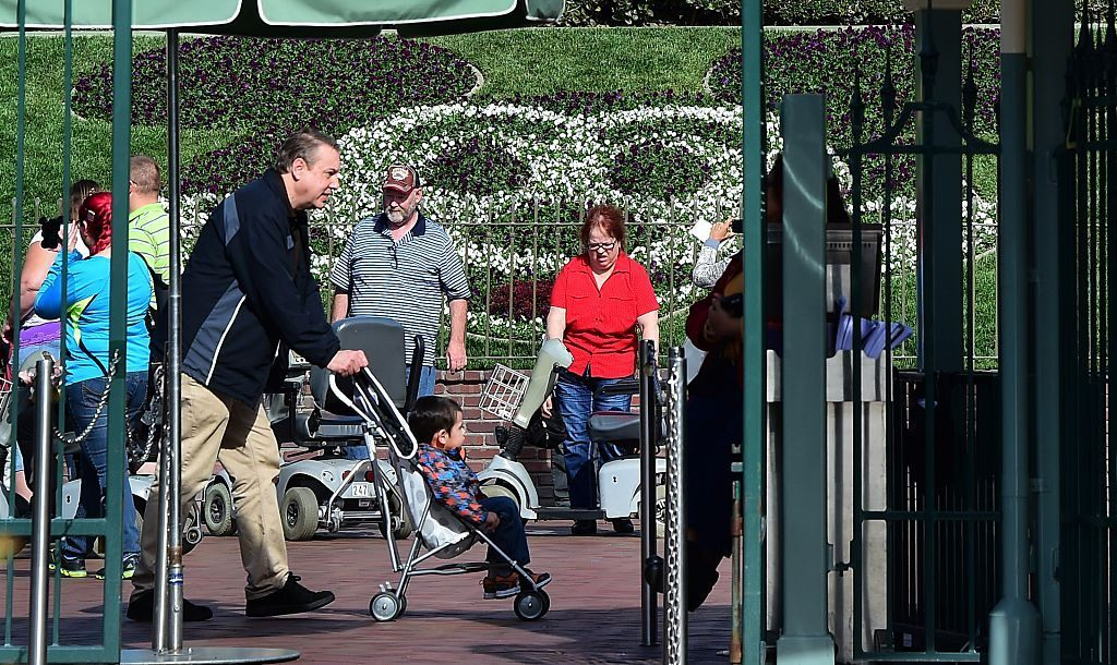 A man pushes a child in a stroller at Disneyland.