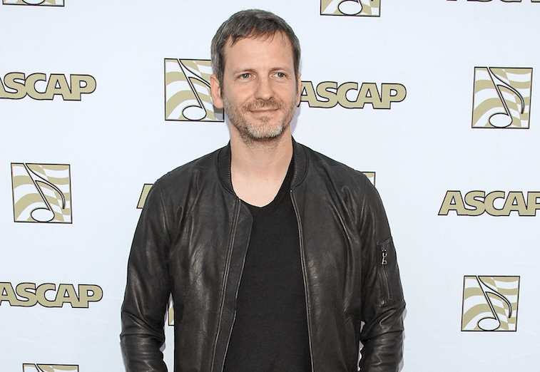 Dr. Luke poses for cameras in a black shirt and leather jacket