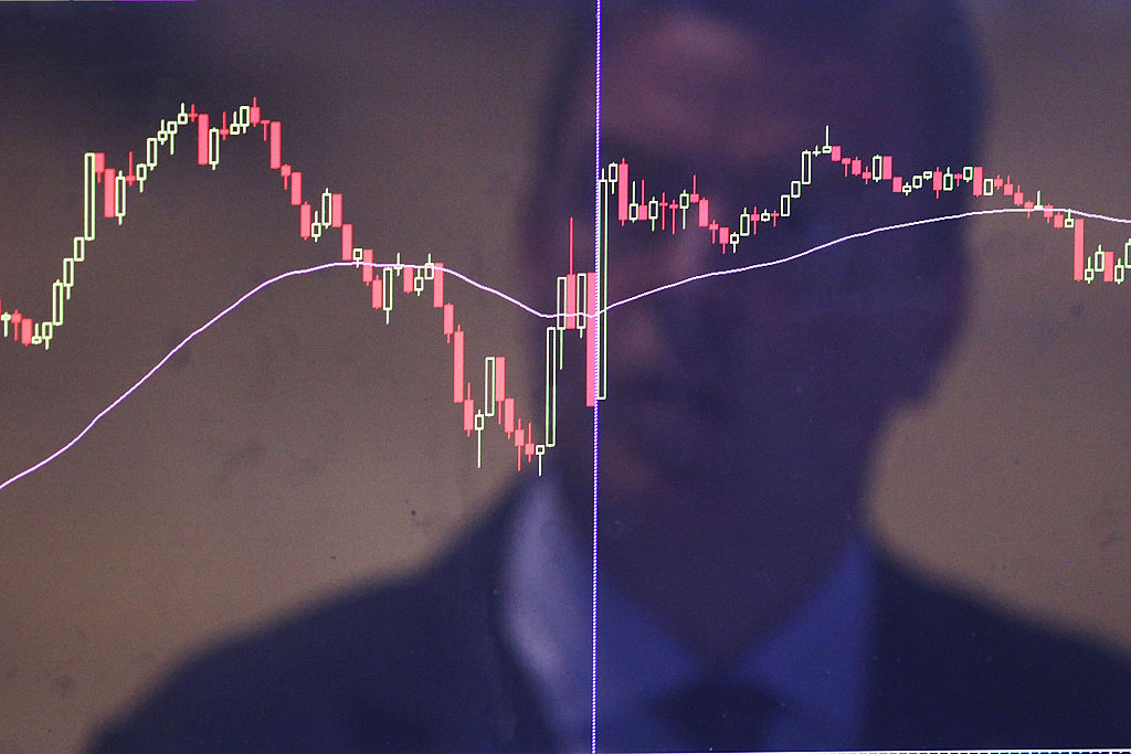 A trader is reflected in a market screen on the floor of the New York Stock Exchange (NYSE)
