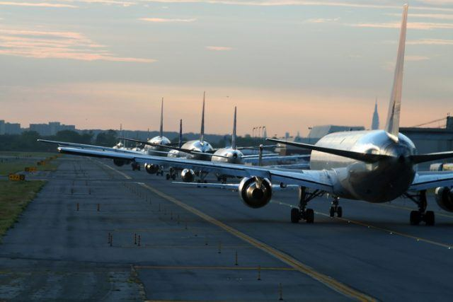 Airplanes on runway at airport during dawn.