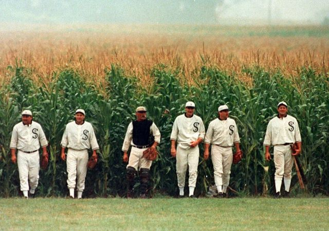 Six men dressed in old baseball uniforms, walking toward the camera out of a corn field