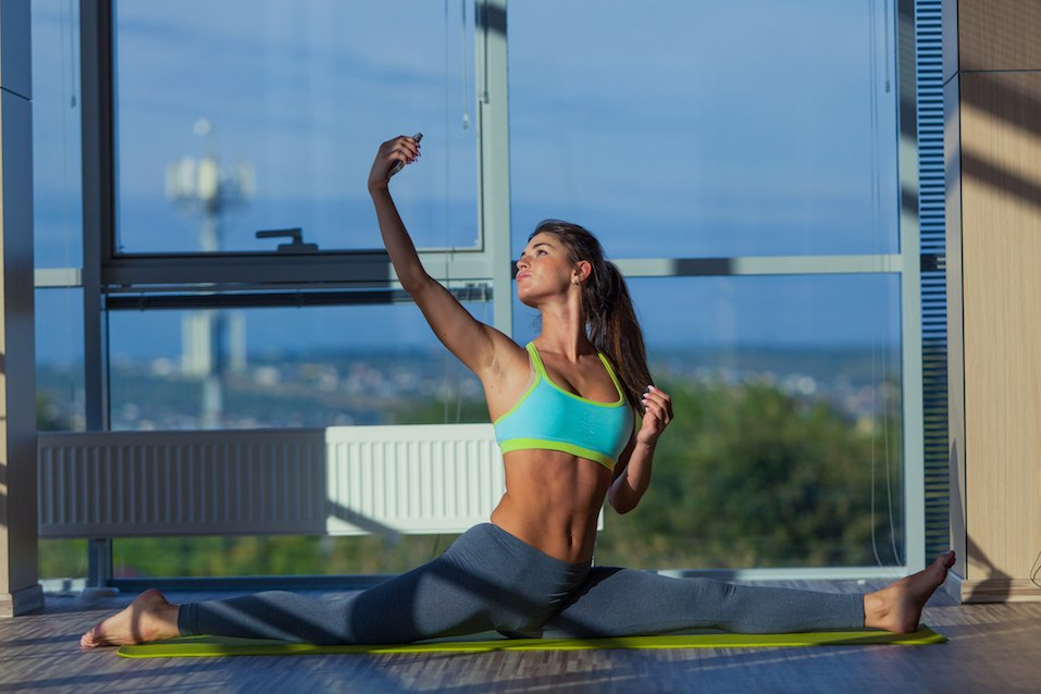 smiling woman stretching on mat in gym. light from a large window selfie