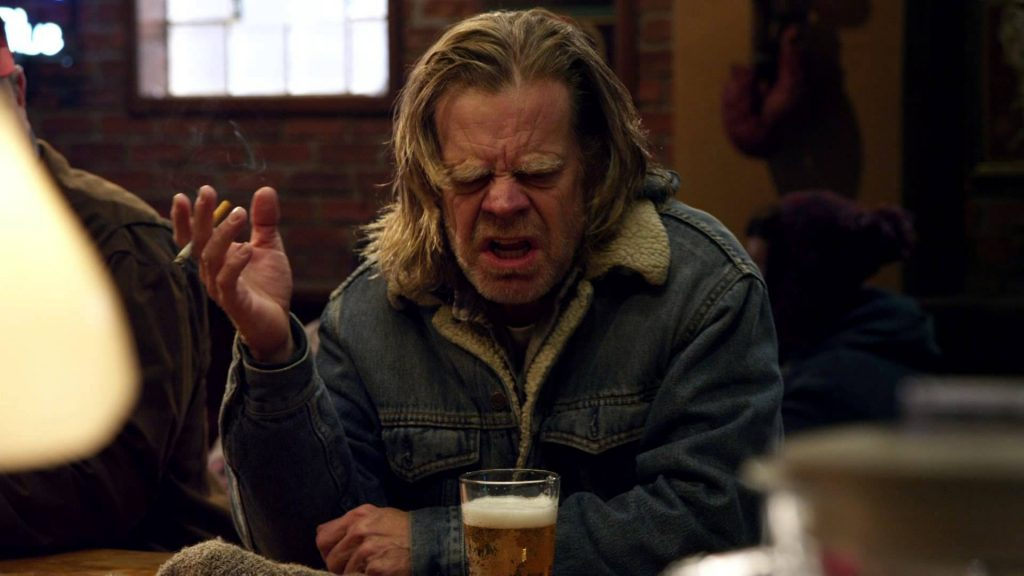 Frank Gallagher, with a cigarette in his right hand, and a beer in front of him, ranting angrily at a bar