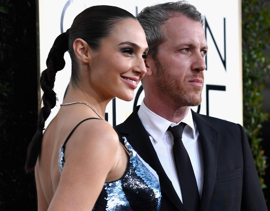 Gal Gadot in a blue dress, smiling on the red carpet with Yaron Versano