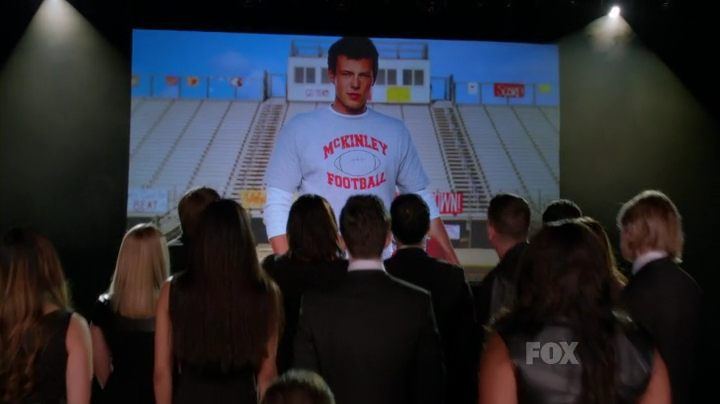 A group of people dressed in back facing away looking at a projected image of a young man posing in a stadium