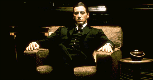 Al Pacino as Michael Corleone, sitting sternly in an armchair and wearing a suit