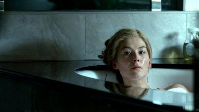 Rosamund Pike, sitting in a bathtub, looking introspectively off into the distance