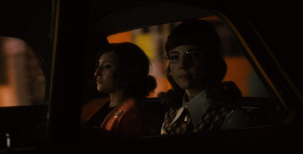 Angie and Cindy sit in the back of a cab looking out the windows