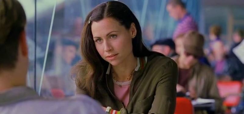 Minnie Driver is sitting at a table looking at Minnie Driver.