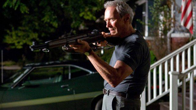 Clint Eastwood aims a shotgun, with late day sun cast across his face