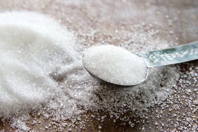 Granulated sugar in spoon and sugar pile on wooden table.