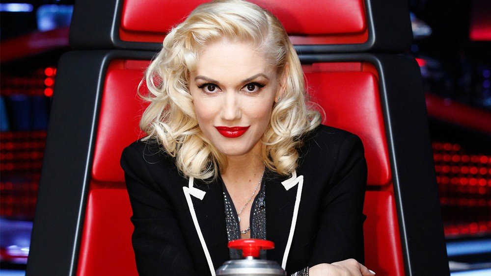 Gwen Stefani sits in her red chair on The Voice