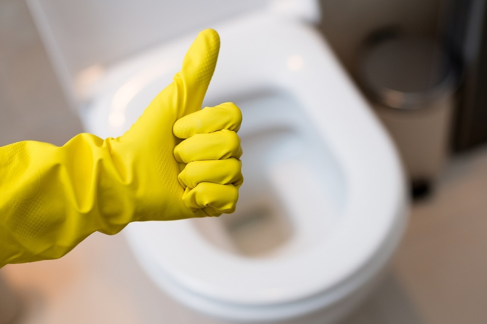 hand in yellow glove giving thumbs up above toilet