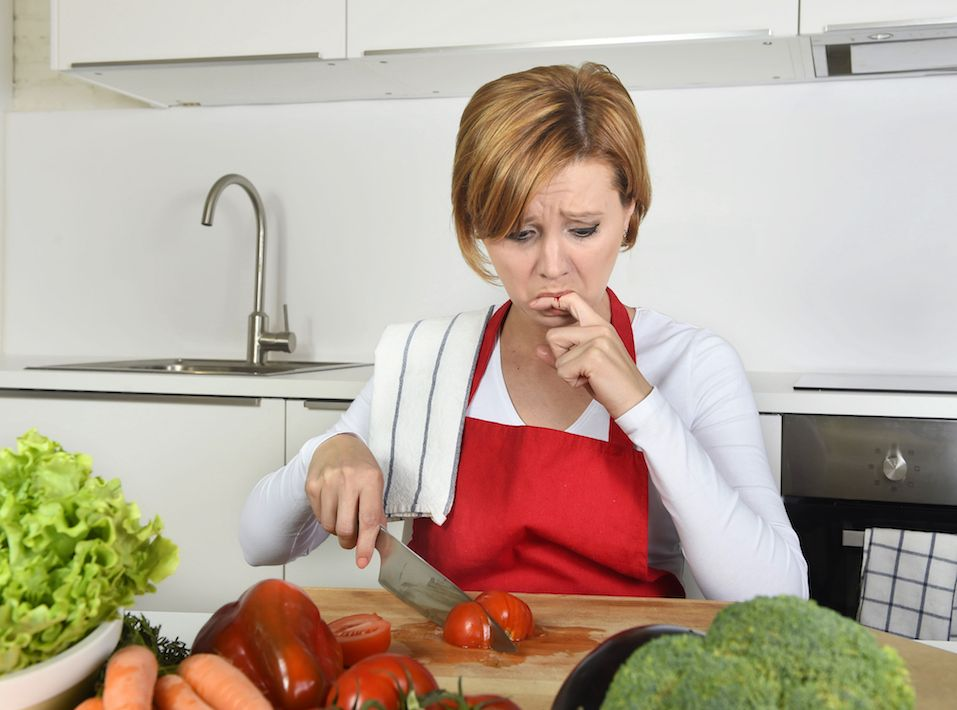 woman in red apron slicing tomato with kitchen knife suffering domestic accident cutting and hurting her finger