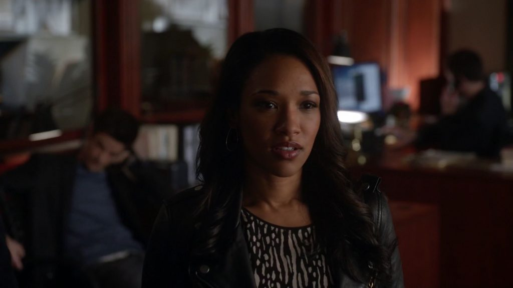 Iris West wearing a black leather jacket, with her mouth slightly open and looking off to the right of the frame