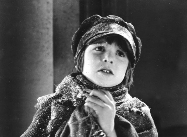 Jackie Coogan wearing winter clothes covered in snow in black and white
