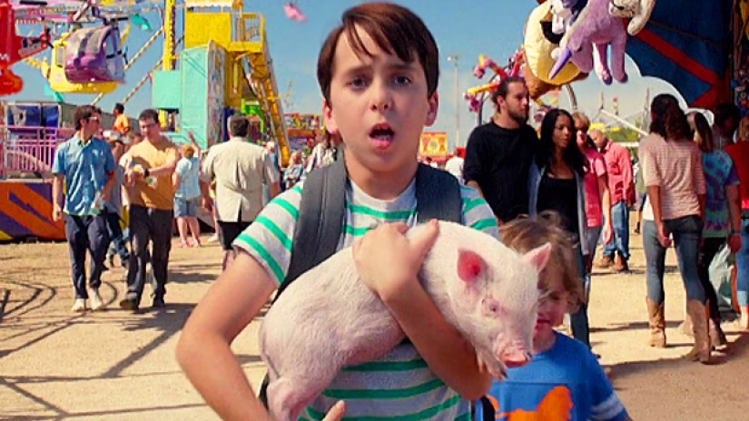 Jason Drucker holds a pig while standing in an outdoor carnival in Diary of a Wimpy Kid: The Long Haul