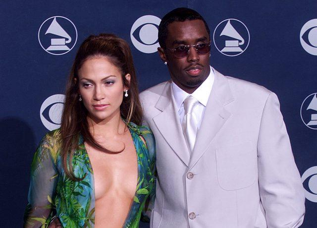 Jennifer Lopez, wearing a green tropical Versace gown with a plunging open neckline, and Sean 'Diddy' Combs, stand on the red carpet at the Grammy Awards.