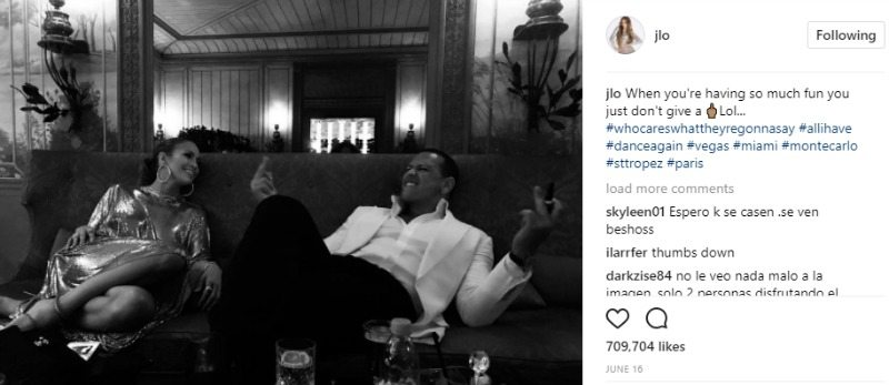 Jennifer Lopez is looking at Alex Rodriguez as he makes a funny face. They are sitting on a couch.