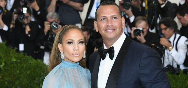 Jennifer Lopez is wearing a blue dress next to Alex Rodriguez who is in a tux
