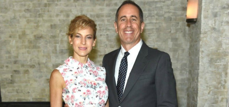 Jerry and Jessica Seinfeld take a picture together in front of a brick wall.