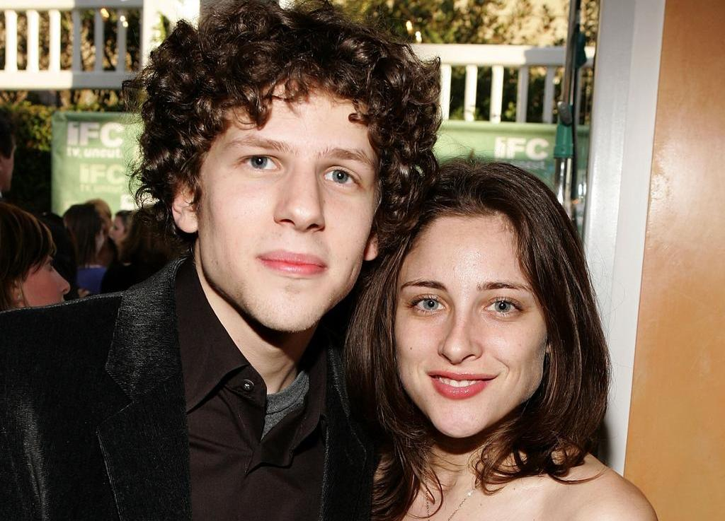 Jesse Eisenberg wearing a black velvet jacket, smiling for the camera with girlfriend Anna Strout