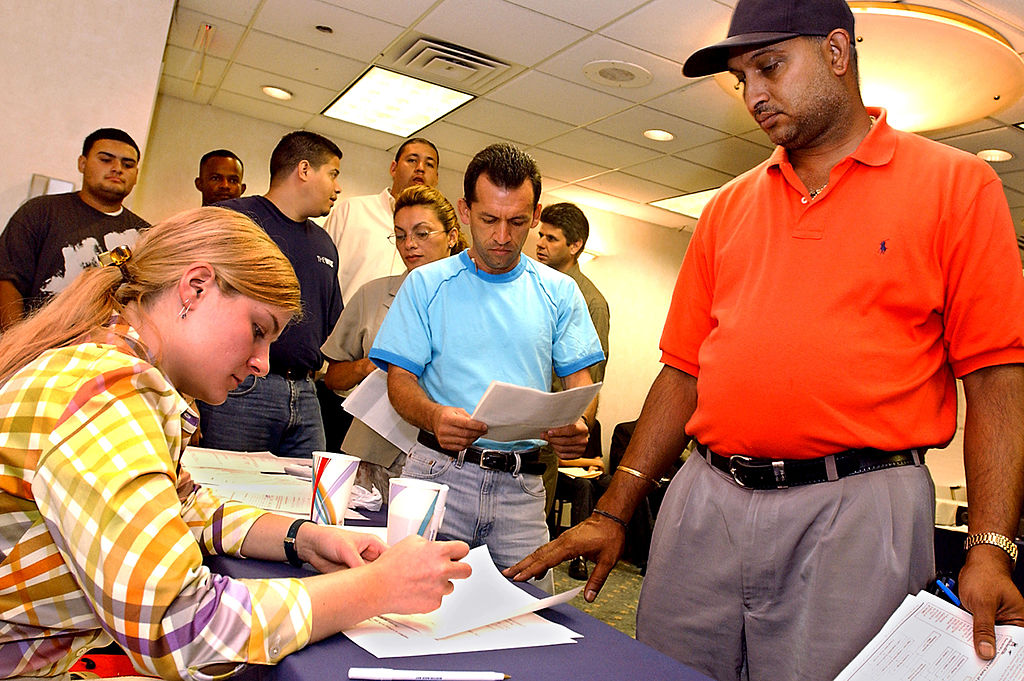 A man stands in line with other applicants as they wait for interview appointments