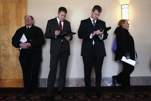 people waiting to interview in black suits