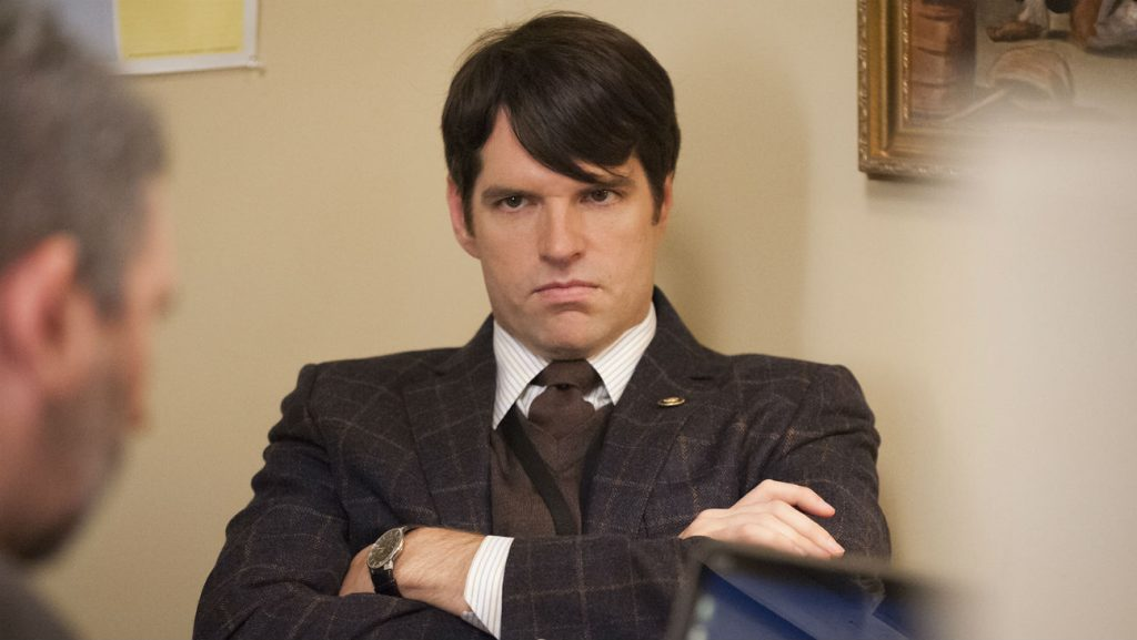 Jonah Ryan wearing a suit, scowling, and crossing his arms defiantly.