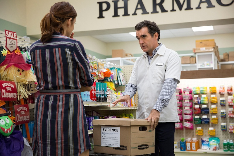 Hannah's parents talk over an evidence box while standing in a pharmacy in 13 Reasons Why