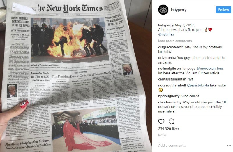 "An Instagram post of Katy Perry's hand holding the front page of the New York Times where there is a picture of a policeman on fire up top and Katy Perry in a red gown on the bottom, with the caption ""All the news that's fit to print"""