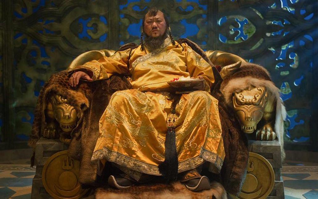 Kublai Khan dressed in a silk yellow robe, sitting atop his thrown with a furrowed brow