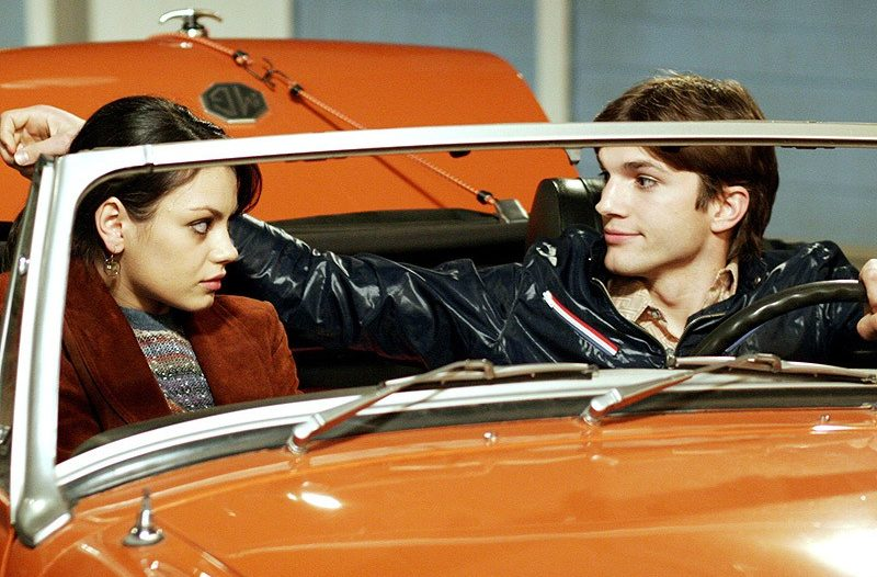 Mila Kunis and Ashton Kutcher sit in an orange car on That '70s Show