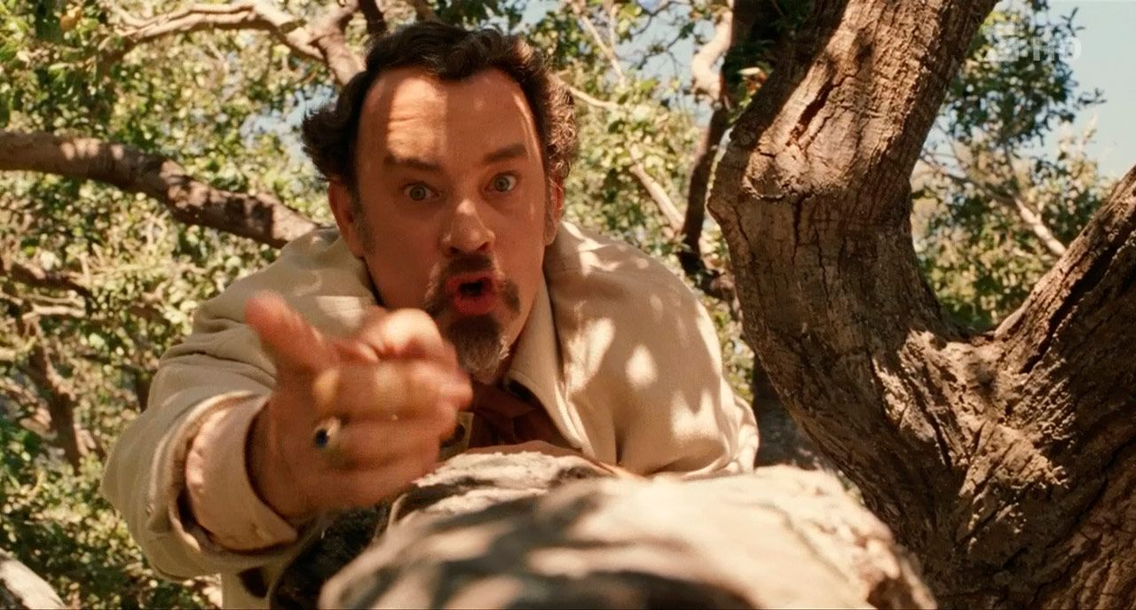Tom Hanks points upwards while climbing a tree in The Ladykillers