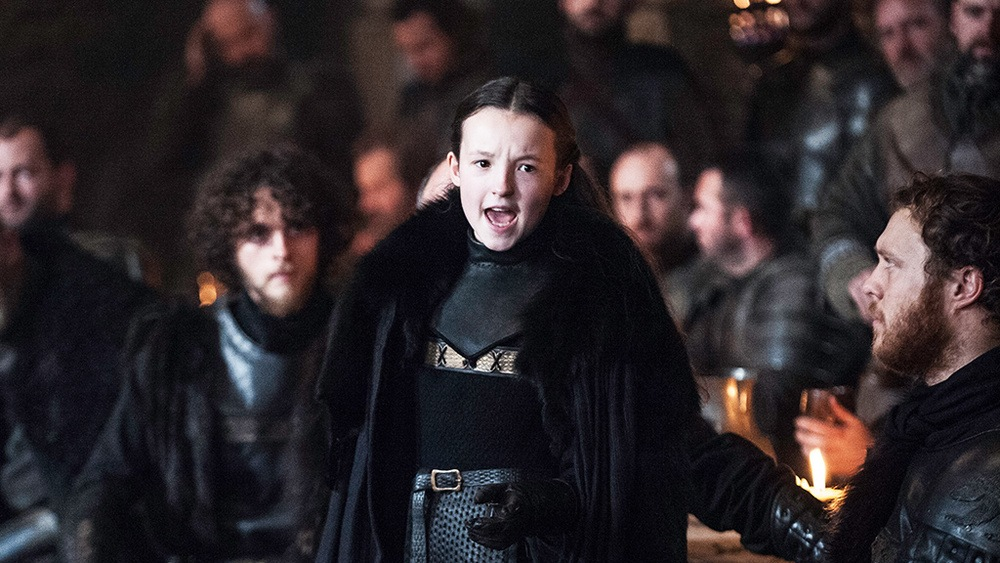 Lyanna Mormont wearing a large black fur coat, speaking to a hall full of men in Winterfell